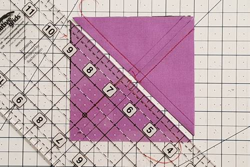 Step 3 3 patch quarter square triangles:  Using a rotary cutter and quilting ruler, cut the squares in half by cutting diagonally from one corner to corner.