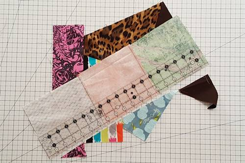 Step 9 Crazy Quilt Block: Choose a side and stitch the new long unit to the main unit using a 1/4 inch seam. Trim the seam.
