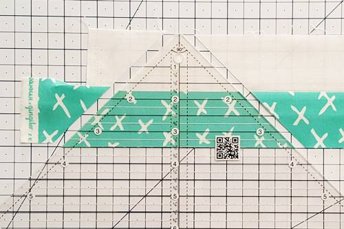 Step 2 Double Hourglass Quilt Block: Press the seam of the strip set toward the darker fabric. Using a rotary cutter, cut the strip along the right and left sides of the ruler, making a QST.