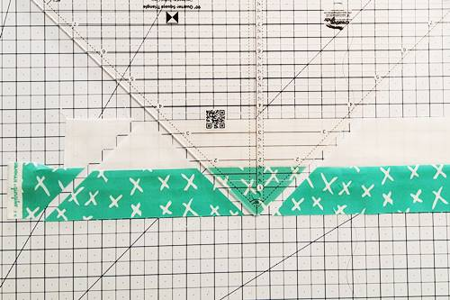 Step 3 Double Hourglass Quilt Block: rotate ruler so blunt tip is along bottom edge of strip set. Align left side of ruler along left side of strip set. Cut along right side of the ruler.
