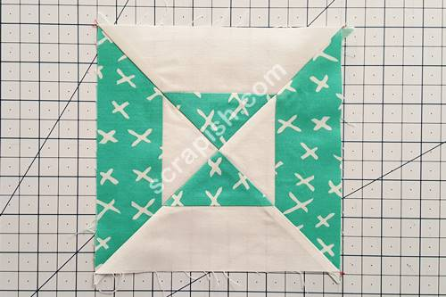 Step 9 Press the seam to one side. Trim off the dog ears. Picture of double hourglass quilt block with dog ears.