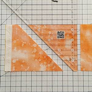 Step 2 Half square triangle ruler: Rotate ruler clockwise. Align blunt tip with bottom of fabric and 45 degree side with 45 degree fabric edge. Cut fabric strips along straight side of the HST ruler.