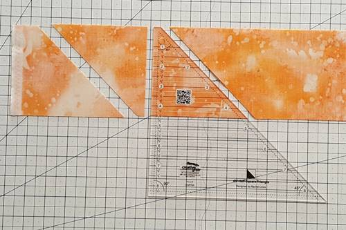 Step 3 Half square triangle ruler: Rotate ruler clockwise 180 degrees. Align blunt end with top of fabric strips. Align the straight side of the ruler with the straight edges of the fabric. Cut.