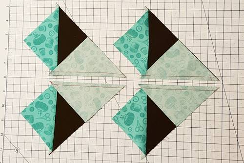 Step 7 No Waste Flying Geese: Place a quilting ruler on the stitched line. Use a rotary cutter to cut both units into two units, making four.