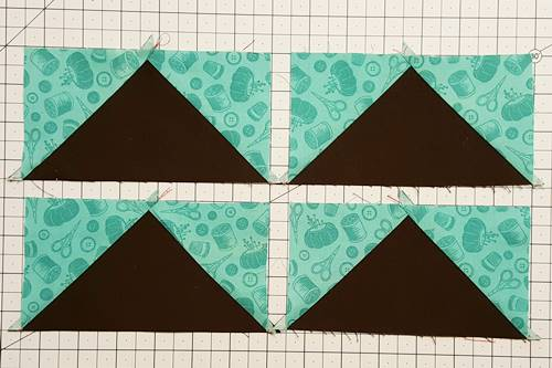 Step 8 No Waste Flying Geese: Flip the triangles face up. Press the seam toward the small triangles.