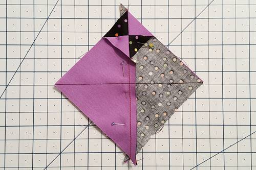 Step 2 Hourglass Quilt Block: right sides together align one of the HSTs on top of the other, like fabrics opposite one another, nest the seams and draw a diagonal line perpendicular to the seam.