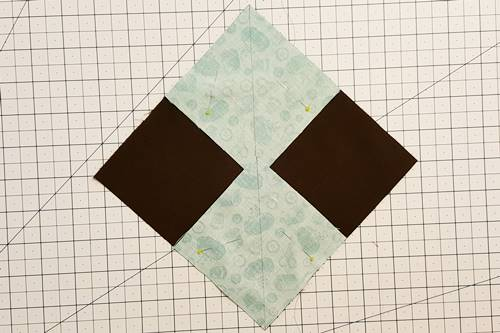 Step 2 No waste flying geese: Place large square right side up; small square, right side down in opposite corners of the large square. Pin.