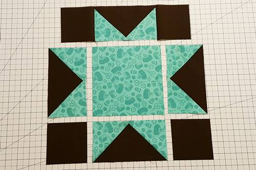 Step 3d Fold the square back right side up. Finger press the seam towards the square. Row 1 units are now sewn together for this star quilt block pattern.